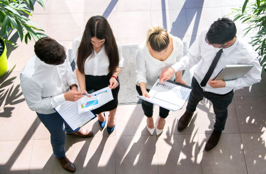 A high angle image of four people in business clothes staring at sheets of paper.