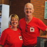 A bald man and blonde woman in red shirts smile at the camera while a chalkboard sign has Donuts written on it.